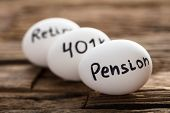 Closeup of pension 401K and retire written on white eggs poster