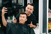 Vietnamese young man taking selfie with hairstylist who did his haircut poster