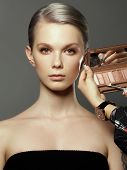 Beautiful girl surrounded by hands of makeup artists with brushes and lipstick near her face. Photo of happy woman on gray background. Grooming himself poster