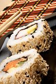 Assorted japanese maki sushi on a black tray with chopsticks ready to be eaten. Selective focus. poster