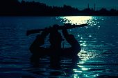 Silhouette of special forces with rifle in action during night raid crossing river in the jungle waist deep in the water. Moon path glowing poster