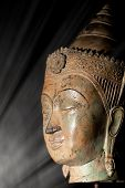 Enlightenment. Spiritual image of a buddha head in a beam of light representing wisdom and an epiphany awakening moment. poster