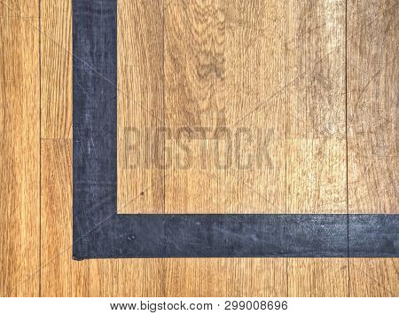 Hall Floor In A Gymnasium With Diverse Lines. Worn Out Wooden Floor Of Sports Hall With Colorful Mar