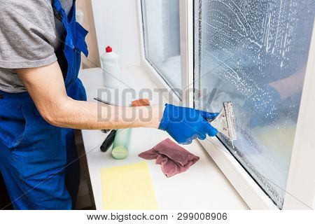 Close-up Of A Man In Uniform And Blue Gloves Washes A Windows With Window Scraper. Professional Home