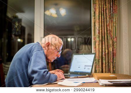 Elderly Man Using A Laptop Computer To Check His Finances ,hampshire,england,u.k.