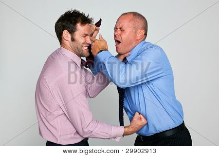 Photo of two businessmen fighting against a plain background, part of a series see my portfolio for them shaking hands and hugging.