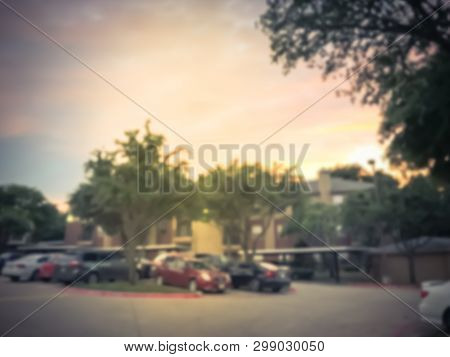 Filtered image blurry background apartment complex detached garage covered parking lots at sunset poster