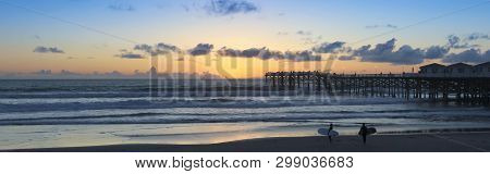 A Panorama Of A Pair Of Sunset Surfers At Crystal Pier In San Diego, California, Usa