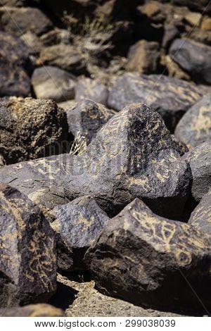 Vertical Shot Of Hohokam Era Petroglyphs On Boulders In The Arizona Desert