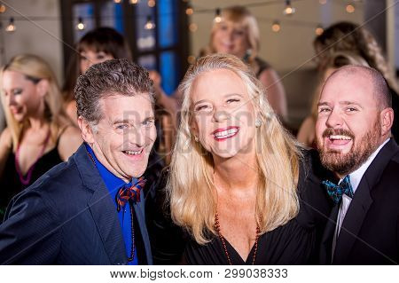 Attractive Mature Woman With Two Male Friends At A Party
