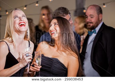 Two Pretty Women Laughing At A Couple Of Men