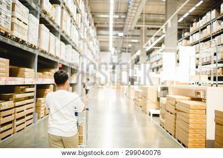 Asian Boy Is Pushing A Shopping Cart In Warehouse For Shopping