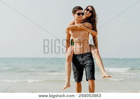 Young Couple Laughing Carrying His Smiling Girlfriend On Back In Love Romance On Travel Honeymoon Su
