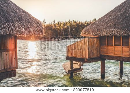Luxury Overwater Bungalows During Sunset Looking Towards A White Sand Beach Filled With Coconut Palm