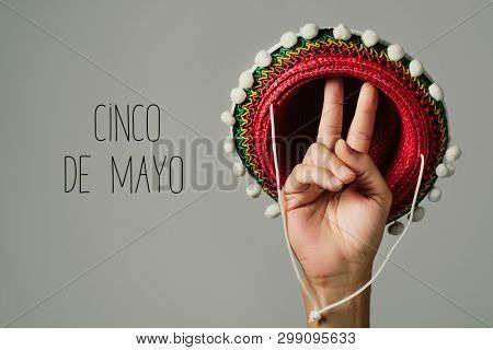 Mexican hat in the hand of a man and the text Cinco de Mayo, May 5 in Spanish, a popular Mexican holiday that commemorates de victory at the Battle of Puebla, written in the colors of the Mexican flag