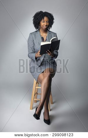 Black Female Author Posing With A Book In A Studio For A Portrait.  She Looks Like A Teacher Or A Wr