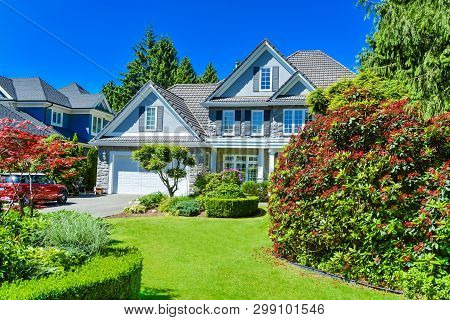 Luxury Residential House With Green Hedge And Landscaping In Front. Family House Surrounded By Trees
