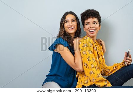 Two smiling young women sitting together and looking away. Happy multiethnic girls having fun isolated on gray background. Beautiful stylish friends laughing while sitting on bench with copy space.