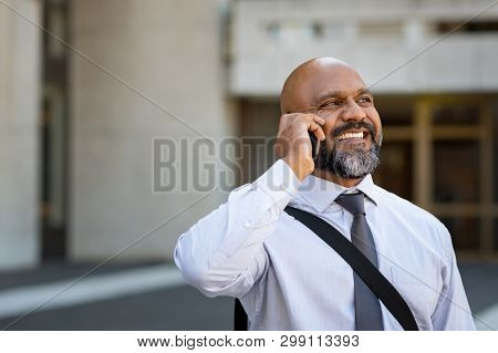 Mature african businessman talking on smartphone outdoor. Happy professional business man using cell phone outside, in city center. Senior man talking on the phone and smiling with copy space.