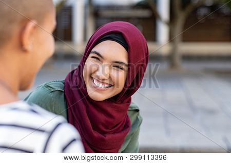 Portrait of cheerful woman in hijab smiling while talking to bald friend. Best friends on street laughing. Back view of beautiful islamic woman with toothy smile looking at friend outdoor.