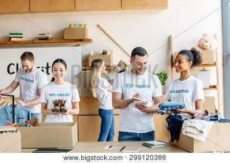 Group Of Young Multicultural Volunteers In White T-shirts With Volunteer Inscriptions Working In Cha