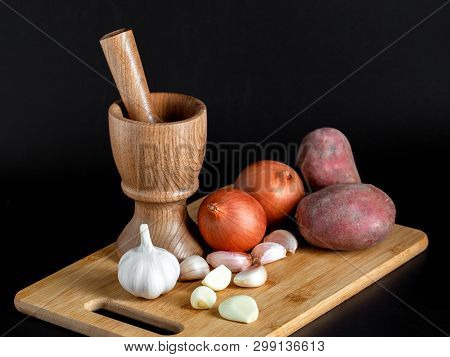 Wooden Mortar (pounder), Pestle, Onion, Garlic And Other Vegetables Isolated On Black