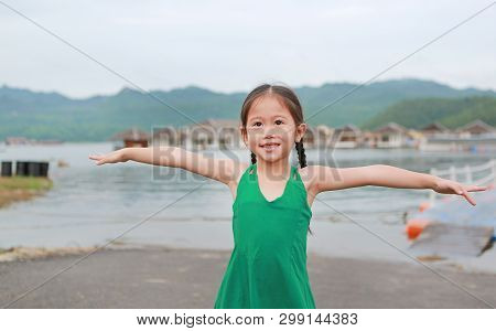 Happy Asian Child Girl Opened Her Hands And Relaxes In Hillside.
