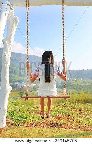 Back Of Young Woman Relaxing By Swing On Hillside At Morning Sunrise.