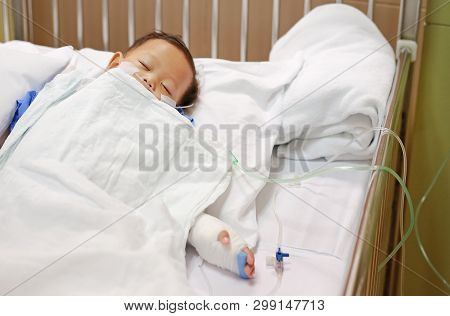 Baby Boy Sleeping With Attaching Intravenous Tube To Hand On Bed At Hospital. Baby Admitted At Hospi