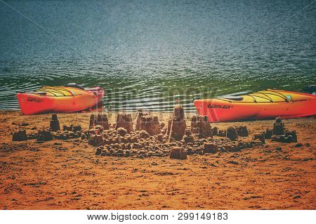 Cary,nc/us-april 28 2019 Sandcastle Surrounded By A Couple Of Canoes On The Lakefront