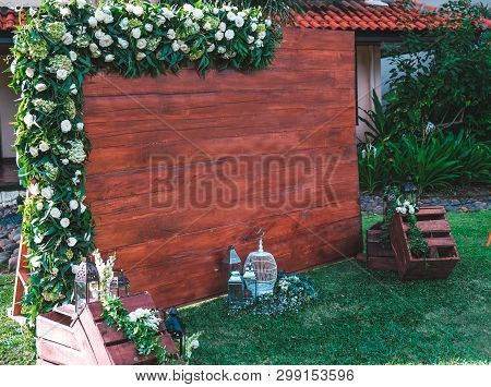 Rustic Wedding Photo Zone. Wedding Decorations Includes Photo Booth, Flowers And Bird Cage. Wedding