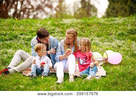 Happy Family On A Picnic In The Flowered Park Sitting On The Grass, Parenthood Leisure In Nature