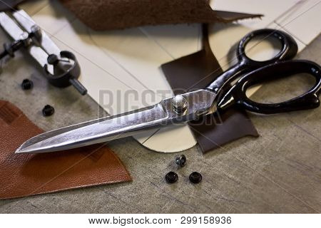 Leather crafting DIY tools and templates on workbench. Fittings and leather pieces with craft instruments for leather items manufacturing. poster