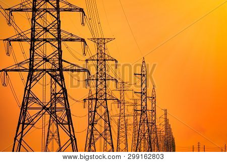 High Voltage Electric Pole And Transmission Lines In The Evening. Electricity Pylons At Sunset. Powe