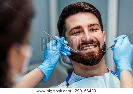 Female Dentists Working On Young Male Patient. Selective Focus. Close Up View.