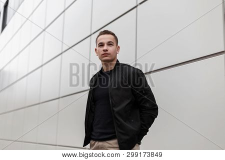 Handsome Stylish Young Man In Vintage Beige Pants In A Black Fashionable Jacket In A Trendy T-shirt