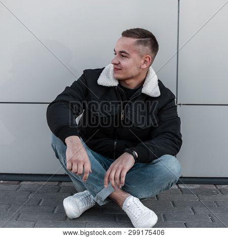 Handsome Attractive Young Man In A Fashionable Black In A Spring Light Jacket Poses Near The Modern
