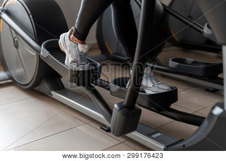 Young Woman Walks In Sportswear On The Stepper Simulator In The Gym. Girl Does Cardio Exercise Exerc