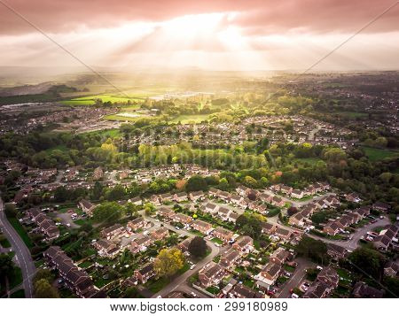 Sun setting with atmospheric effect over traditional British houses and tree lined streets. Dramatic