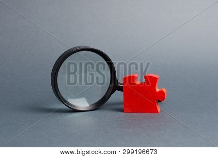 Red Puzzle And Magnifying Glass. The Concept Of Finding The Missing Detail Or Element In The General