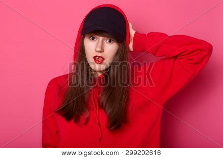 Portrait Of Surprised European Brunette Teenager Keeps Her Hand On Head, Stands With Open Mouth, Dre