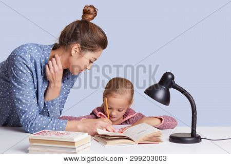 Close Up Portrait Of Young Mum Helps To Write Her Daughter To Write Composition, Use Reading Lamp, G