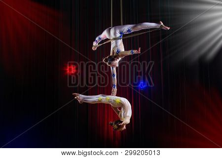Circus Actress Acrobat Performance. Two Girls Perform Acrobatic Elements In The Air.