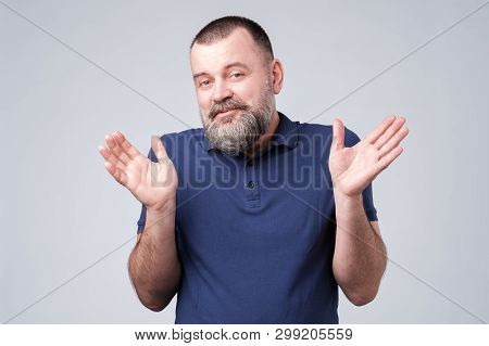 Bearded Man In Blue T-shirt Shrugging Shoulders