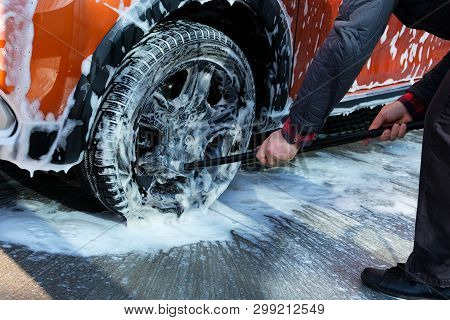 Cleaning With Soap Suds At Self-service Car Wash. Man Washes Black Wheel Of His Orange Car With Brus