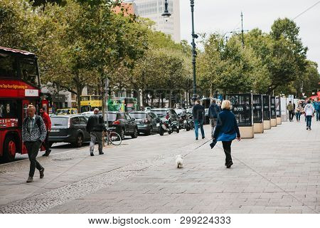 Berlin, October 1, 2017: City Street With People And Cars. Normal City Life. A Woman Walking A Dog,
