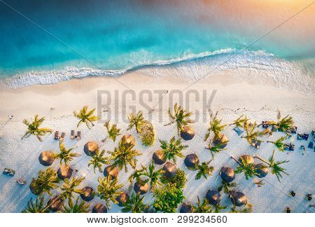 Aerial View Of Umbrellas, Palms On The Sandy Beach Of Indian Ocean At Sunset. Summer Holiday In Zanz