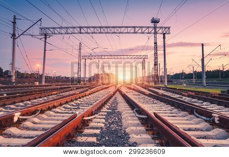 Modern Railway Station At Night In Europe. Industrial Landscape With Railroad Junction, Colorful Sky