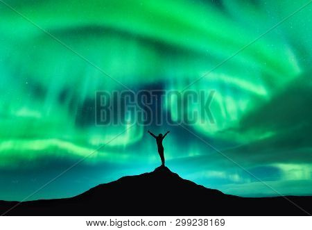 Aurora Borealis And Silhouette Of A Woman With Raised Up Arms On The Mountain Peak. Lofoten Islands,