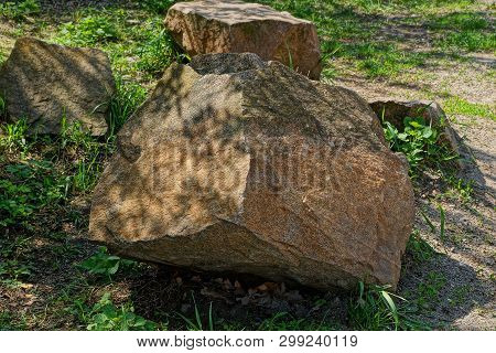 Big Brown Stones Lie In The Green Grass On The Nature In The Park